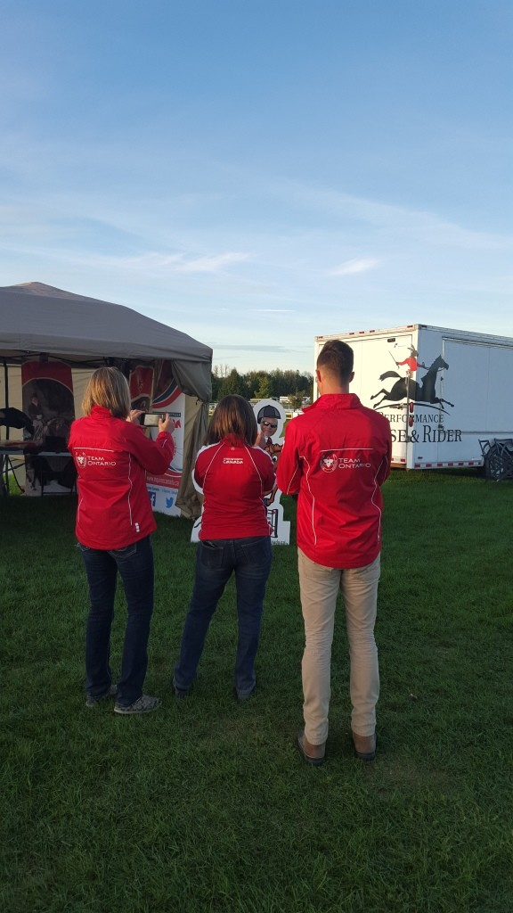 Ellen Dvorak, Simone Williams and Brandon Hall, enjoying taking a picture of Tom Dvorak in the Equine Canada Horse display!