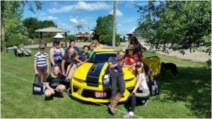 Supermodel poses with the fancy cars - Team Oakhurst does it with style.